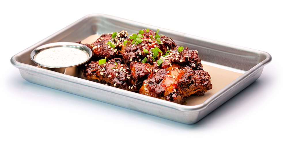 Asian style chicken wings with sauce on silver serving tray