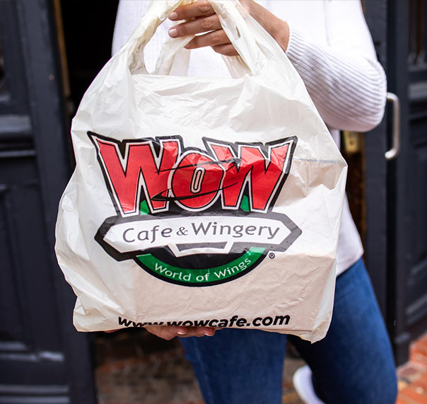 Guest holding bag of WOW World of Wings delivery order