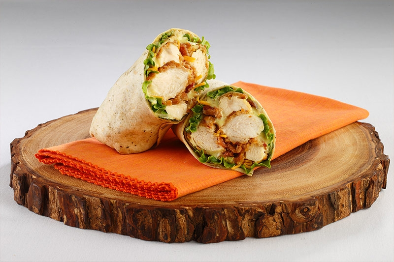 Chicken wrap presented on top of napkin and wood table