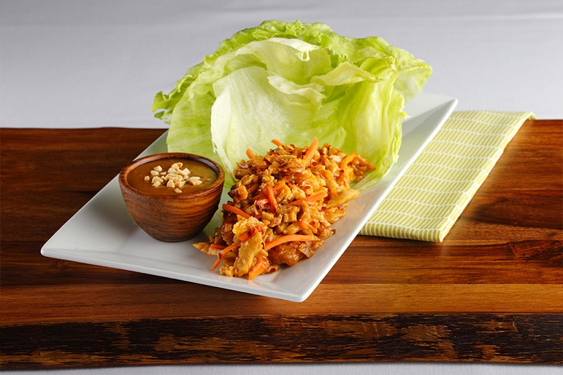 Lettuce wraps shown on white plate sitting on a wood table