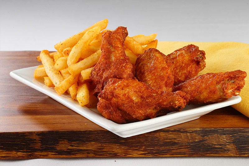 Traditional WOW wings served with fries on white plate on wood table