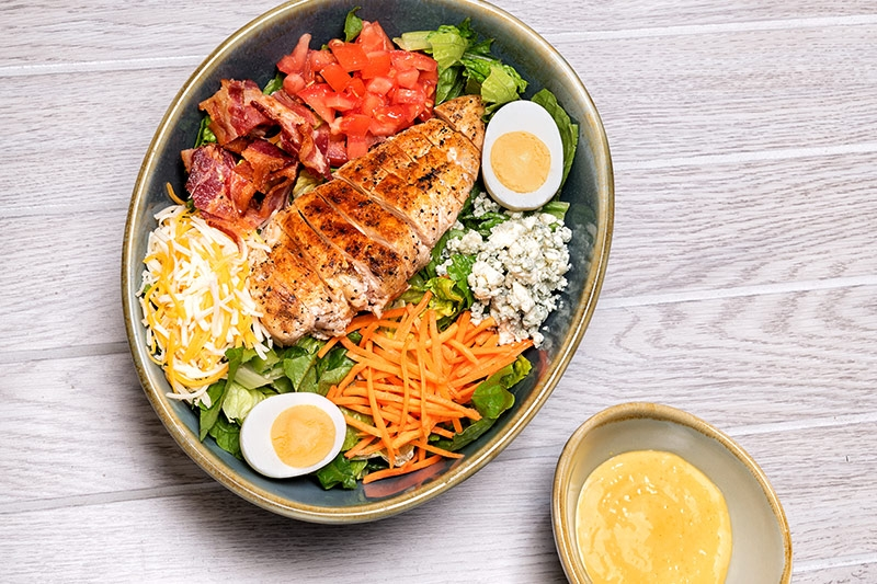 Grilled Chicken Cobb salad shown overhead in dark serving bowl on wood table
