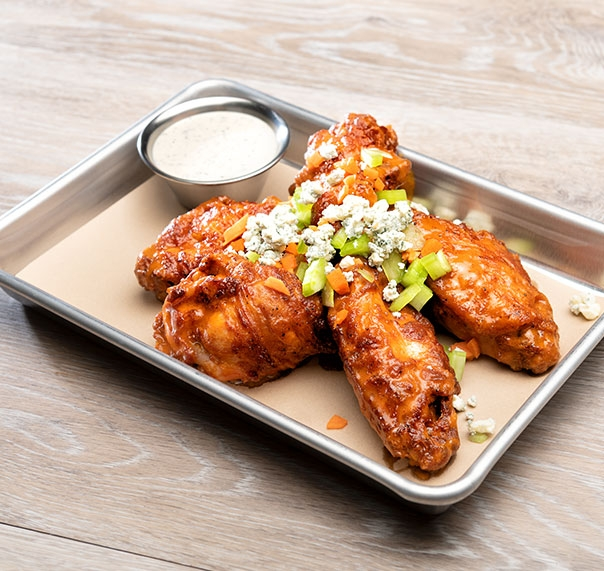 Buffalo chicken wings dressed with blue cheese shown on silver serving tray