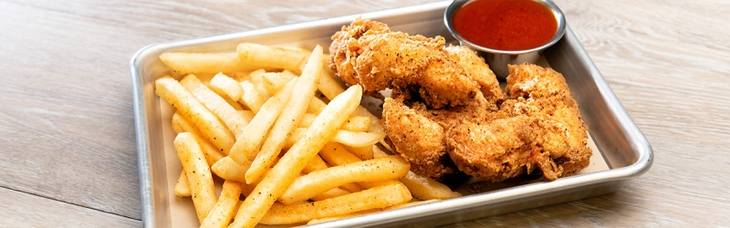 Chicken tenders served with fries and sauce on silver serving tray
